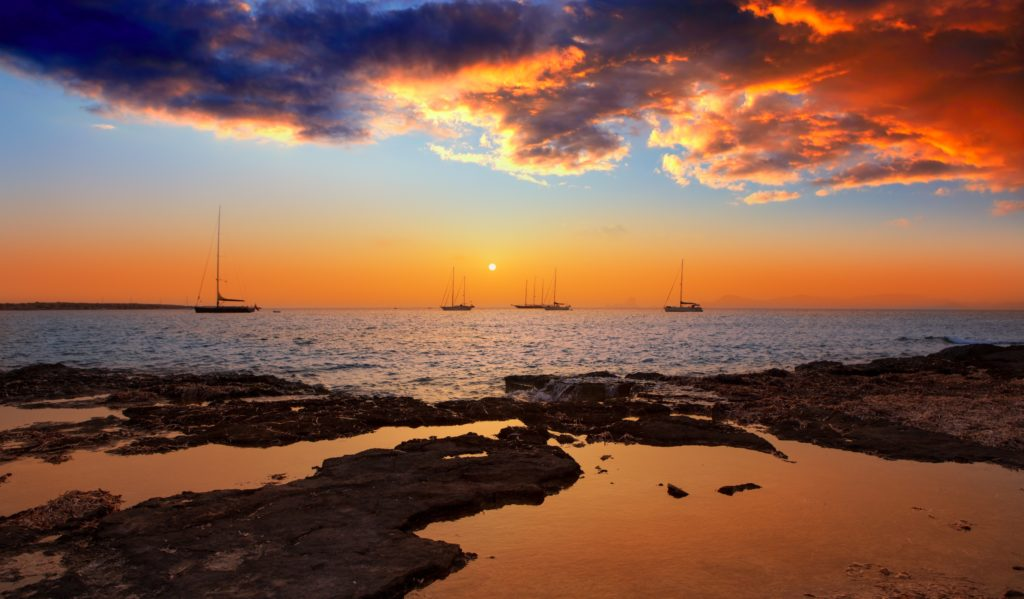 View of a sunset from the beach showing 5 sailboats in the background