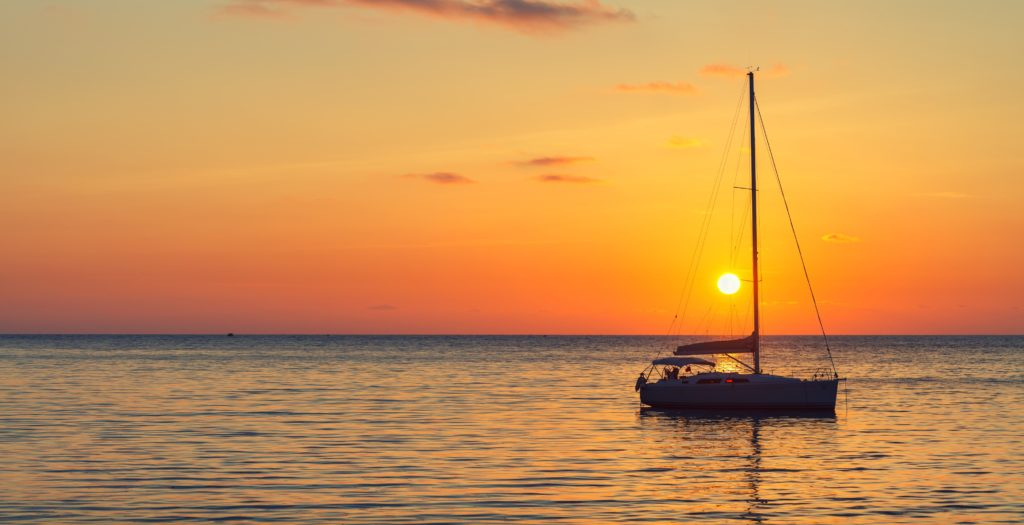 View of a sailboat in the sunset in the middle of the sea