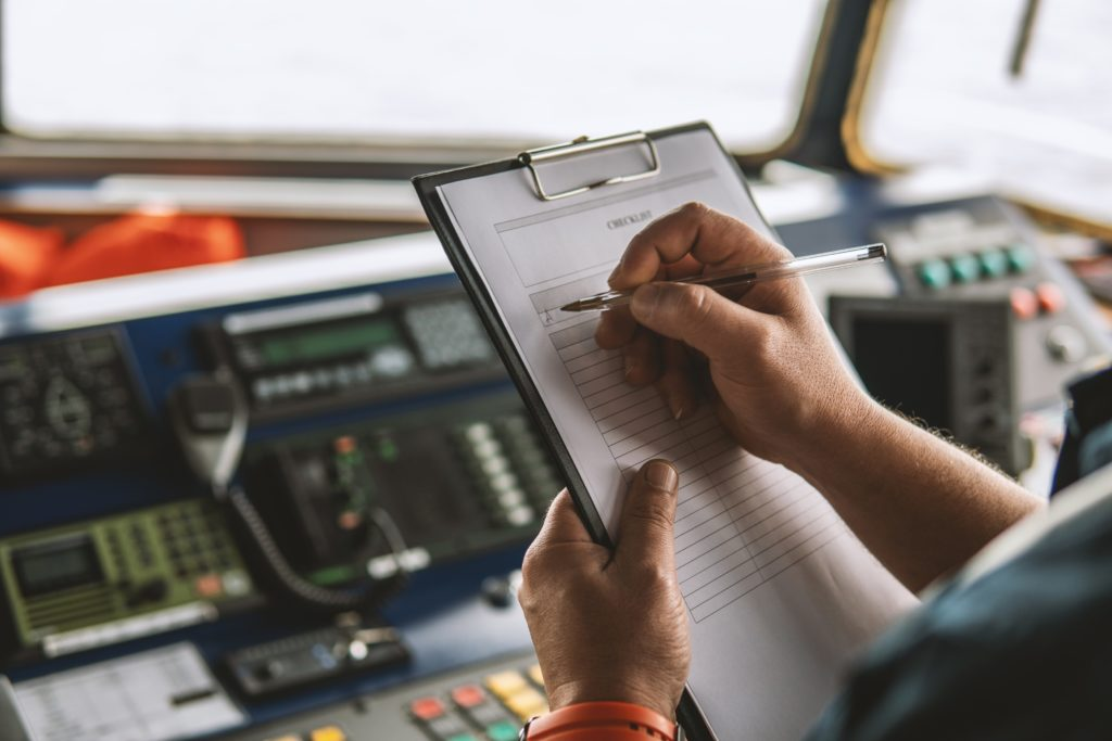 Image of a man making notes for the journey ahead on a sailboat