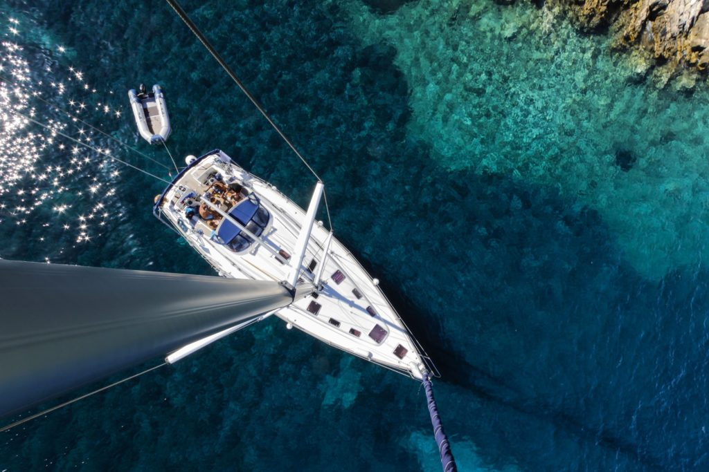 Aerial view of a sailboat with people staying on the deck