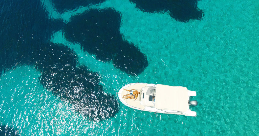 Aerial view of a couple on a boat in the middle of the sea