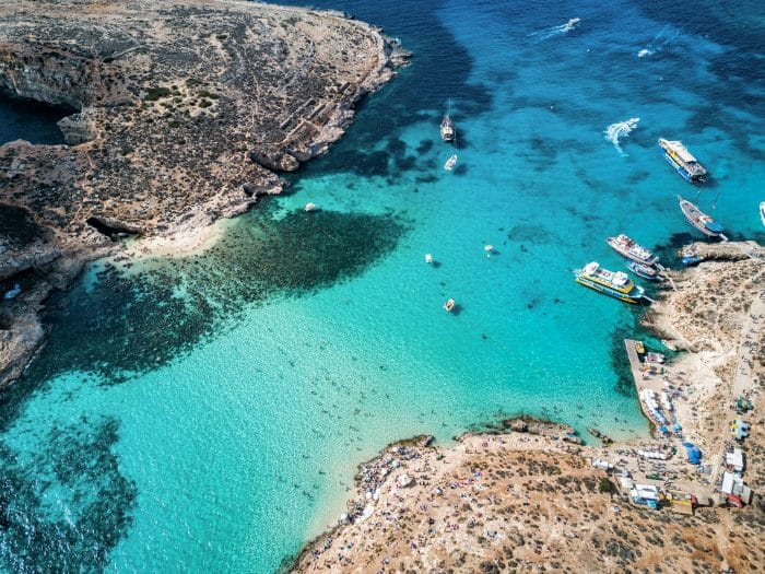 Aerial view of Comino with the stunning cliffs and anchoring boats in crystal clear water
