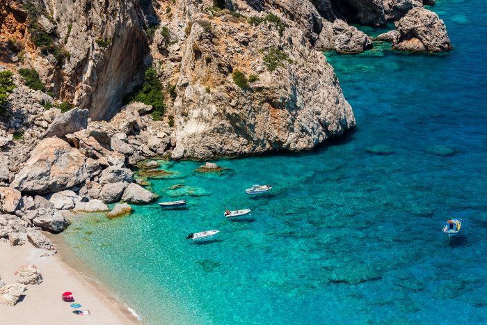 Beautiful bay in Alonissos surrounded by cliffs and some anchoring boats